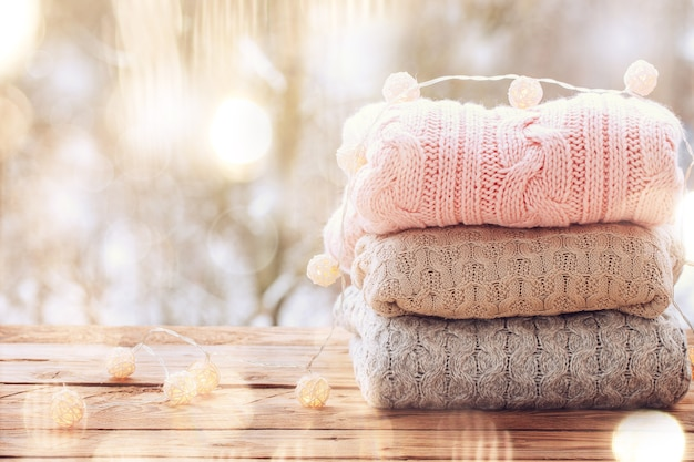 Cozy pile of wool knitted sweaters on wooden table on winter nature background