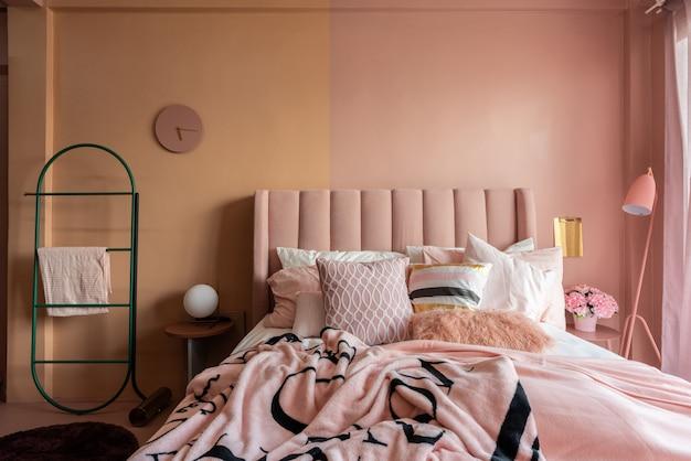 居心地の良いピンクのベッドルームコーナー、ベビートーンのピンクのベルベットの布製ベッド、毛布、枕、ピンクのフロアランプ、ツートンピンクの塗装壁
