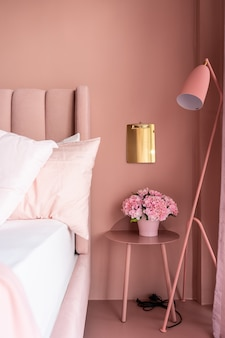 Cozy pink bedroom corner with baby pink velvet fabric bed decorated by blanket, pillows and pink floor lamp with two-tone pink painted wall