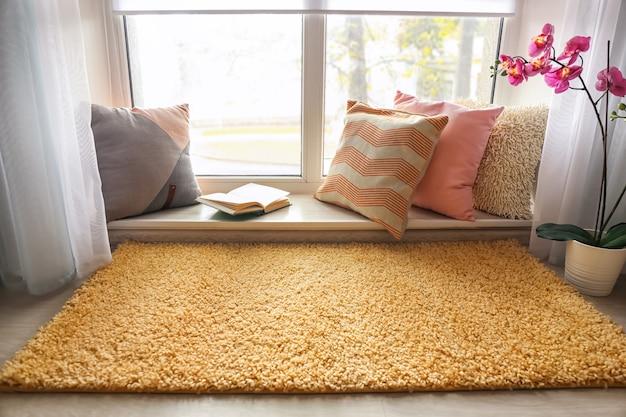 Уютное место для отдыха с мягкими подушками и книгой у окна