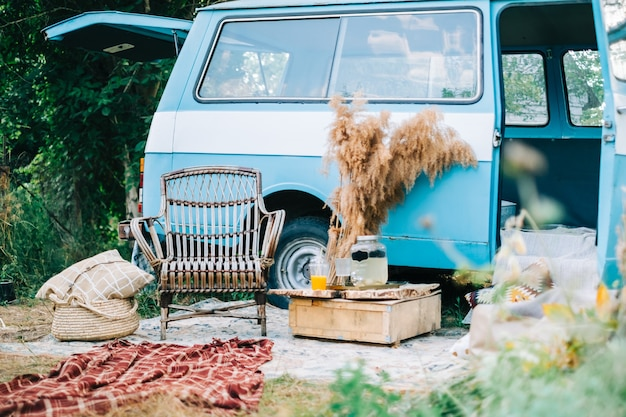 Cozy place near blue van with wooden chair and mini table.