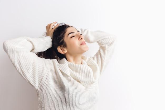 기분 좋은. 편안한 부드러운 긴 소매 흰 벽에 고립에서 아름 다운 갈색 머리 여자의 초상화. 가정의 편안함, 감정, 표정, 겨울 분위기 개념. copyspace.