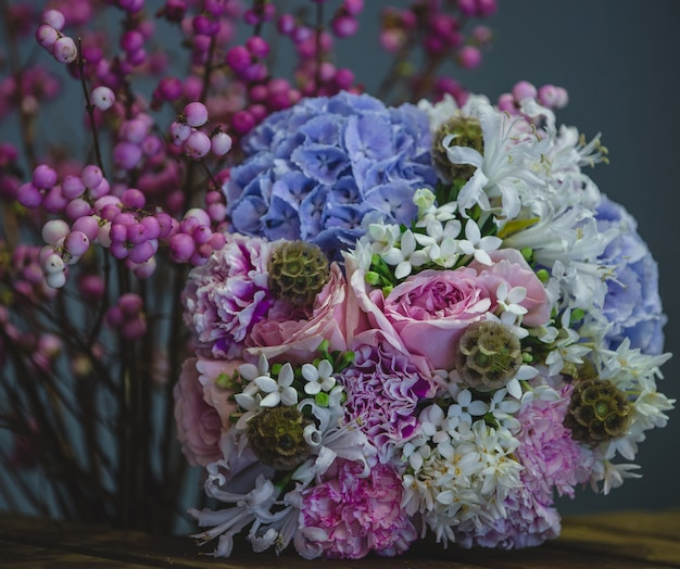 A cozy, pretty bouquet of blue and purple combination of flowers.