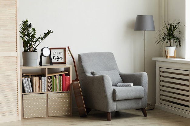 Cozy reading nook in modern minimal interior, focus on grey armchair against white wall