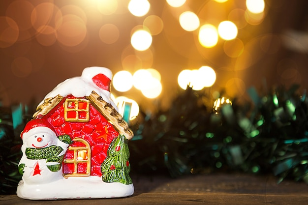 Уютный красный пряничный домик с подсветкой в окне и снеговиком на деревянном фоне с copyspace и defocus огнями в боке. новый год, рождество, праздник фон, дома
