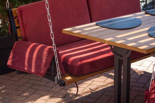 Уютные красные качели на цепочках вместо стульев в летнем ресторане курортного городка