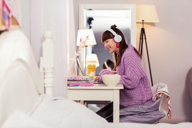 Уютная комната. радостный подросток сидит в полу-положении и смотрит на свой ноутбук