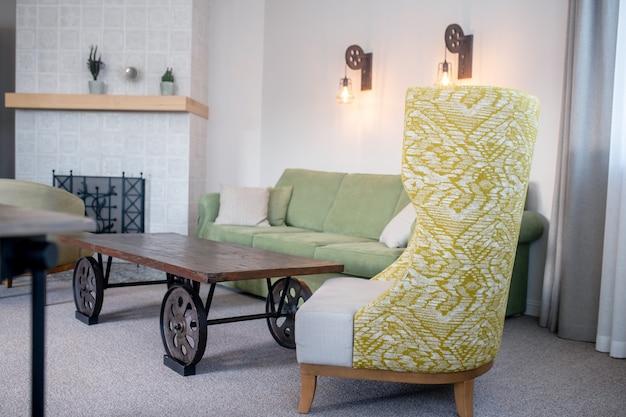 居心地の良い部屋。落ち着いた色調の柔らかな家具と、日光の下で暖炉のある部屋の車輪付きの低いテーブル