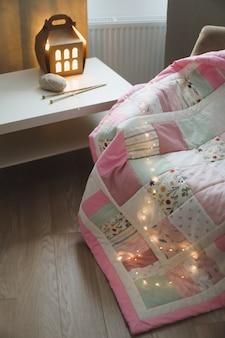 Уютная комната с креслом с одеялом из шерстяной пряжи и спицами на столе у окна.