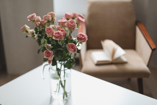 Уютная комната с цветами в вазе, креслом и книгой Premium Фотографии