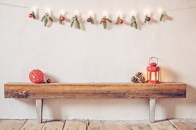 Cozy rustic christmas composition in a rural house with a lantern and red bauble on an old wooden log