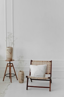 木の花瓶に花が置かれた木のコーヒー テーブルの隣、床の花瓶の隣に枕が置かれた籐の椅子の居心地の良いスカンジナビア インテリア