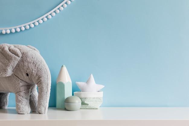 Уютная скандинавская детская комната для новорожденных с серым плюшевым слоником, лампой с белыми звездами и детскими аксессуарами.