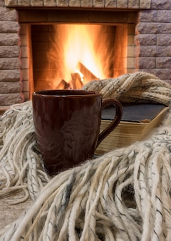 Cozy scene before fireplace with brown mug with tea, a book, wool scarf.
