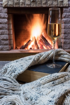 Cozy scene before fireplace with glass of wine, book and wool warm scarf.