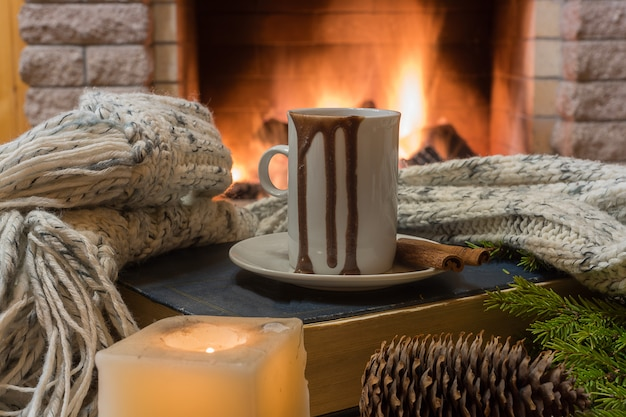 Cozy scene before fireplace with mug of hot chocolate, cone, candle and wool scarf.