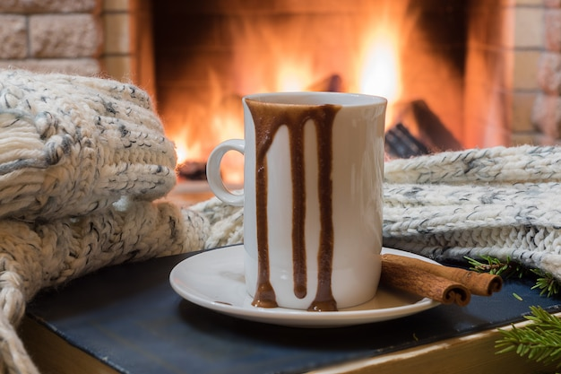 Cozy scene before fireplace with mug of hot chocolate, and wool scarf.