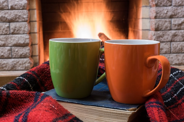 Cozy scene before fireplace with orange and green mugs with tea, and wool scarf.