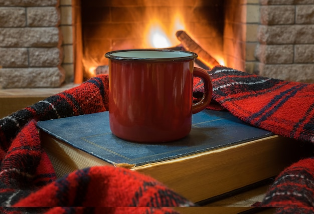 Cozy scene before fireplace with red enameled mug with tea, a book, and wool scarf.