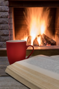 Cozy scene before fireplace with red mug of tea, and opened book.