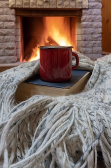 Cozy scene before fireplace with red mug with tea, a book, wool scarf.