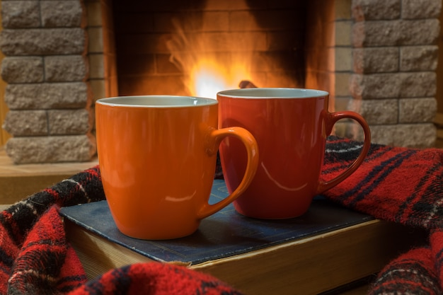 Cozy scene before fireplace with red and orange mugs with tea, a book, wool scarf.