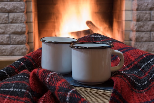 Cozy scene before fireplace with two enameled mugs with tea, a book, wool scarf.