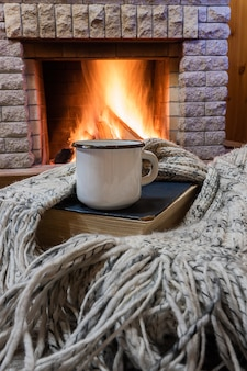 Cozy scene before fireplace with white enameled mug with tea, a book, and wool scarf.