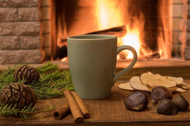 Cozy scene near fireplace with mug of hot chocolate , tangerine, cones and cinnamon sticks