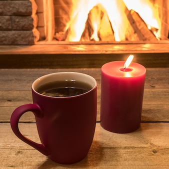Cozy scene near fireplace with mug of hot tea and candle.