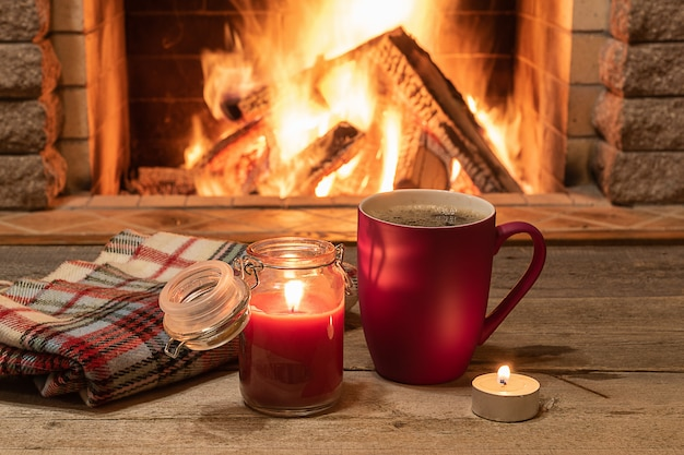 Cozy scene near fireplace with mug of hot tea, warm scarf and candle.