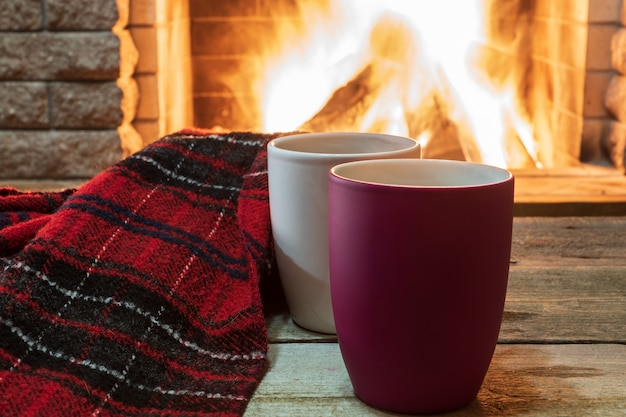 Cozy scene near fireplace with mugs of hot tea and warm scarf.