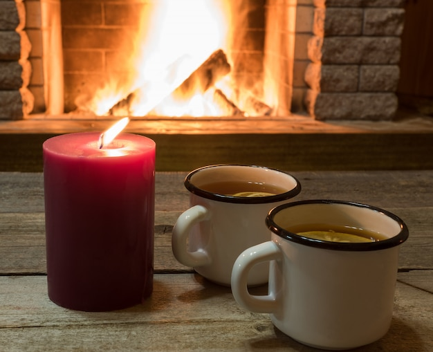 Cozy scene near fireplace with two white mugs of hot tea and purple candle.