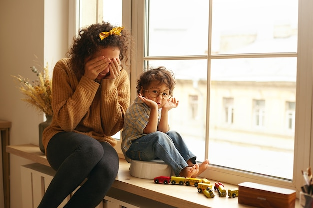 屋内で幸せな家族の居心地の良いシーン。巻き毛の魅力的な若い女性は、母性の甘い瞬間を楽しんで、大きな窓辺に座って、愛らしい幼児の子供とかくれんぼをしています