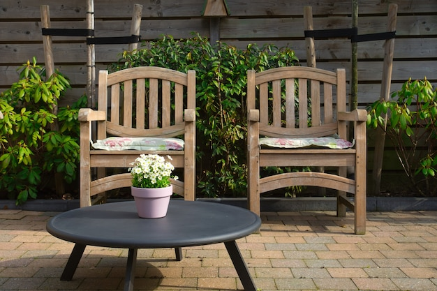 Cozy seating area in the garden of a modern home in the spring wooden seats with colorful flowers in flower pot
