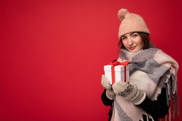 Cozy shot of charming happy cute young brunette woman isolated over red background