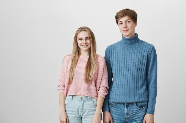 室内でポーズをとってニットのセーターを着ている白人の友人の居心地の良いショット。かわいい金髪のガールフレンドの後ろに立っている金髪と青い目を持つ流行に敏感な男
