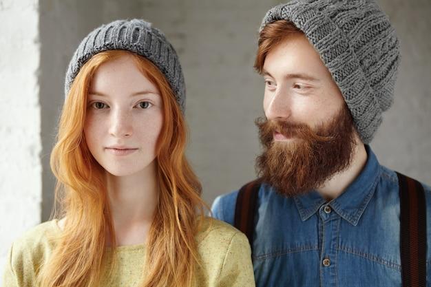 Уютный снимок двух красивых кавказских друзей в серых вязаных шапках, позирующих в помещении.