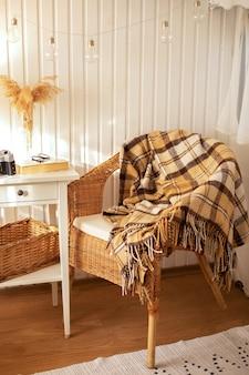 Уютный дом в скандинавском стиле с плетеным креслом из ротанга и пледом