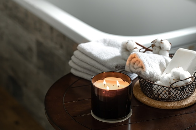 양초와 목욕 수건, 비누 및 면화 장식의 향기의 아늑한 스파 구성. 바디 케어 및 위생 개념.