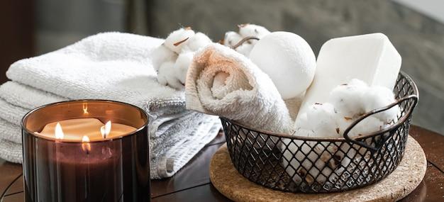 촛불과 목욕 수건, 비누의 향기의 아늑한 스파 구성. 바디 케어 및 위생 개념.