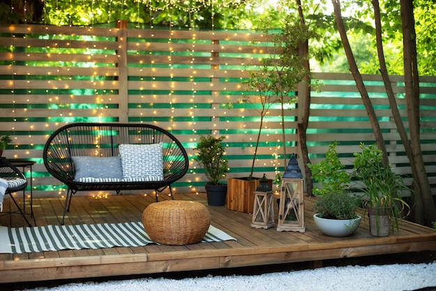 Cozy space in patio with plants wooden wall and table comfortable sofa and lanterns