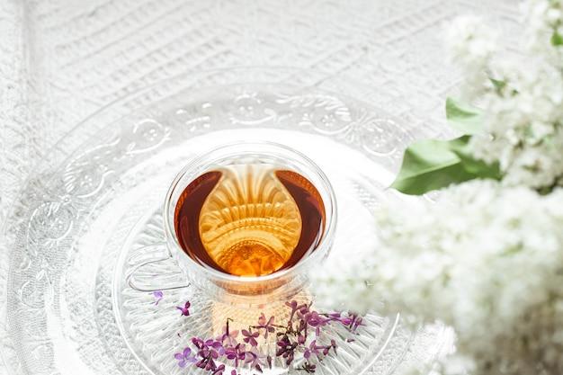 Уютная весенняя композиция с чаем и цветущей сиренью. вид сверху, плоская планировка