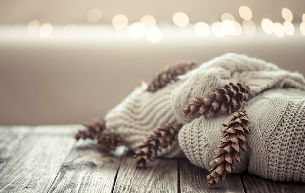 A cozy stack of knitted sweaters with pine cones