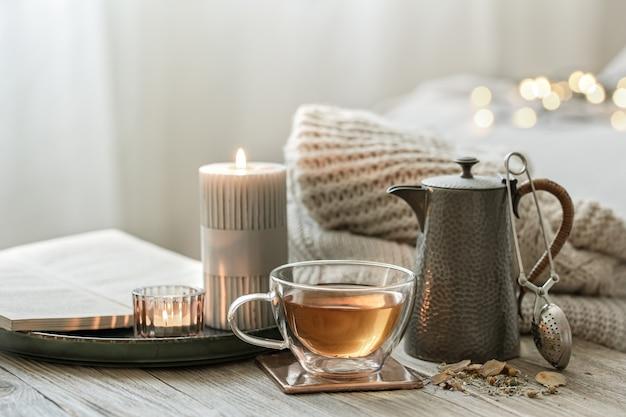 お茶、ティーポット、キャンドルをボケ味のあるぼやけた背景に置いた、居心地の良い静物画。