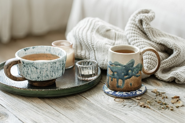 Cozy still life with ceramic cups with tea and a knitted element.