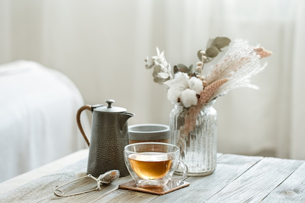 Cozy still life with glass cup of tea, candles and knitted element on blurred background copy space.