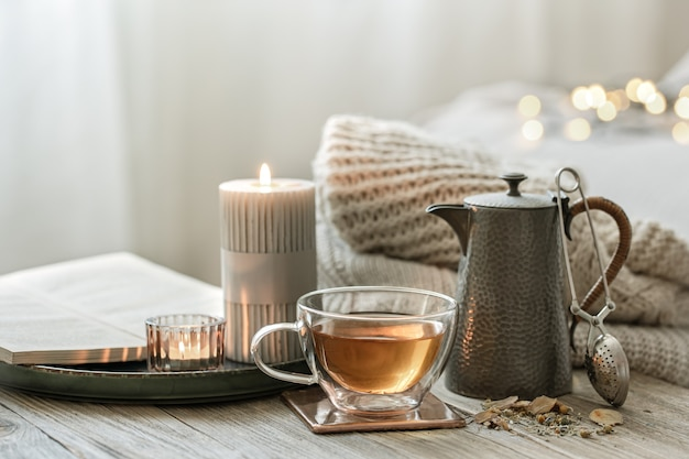 Cozy still life with a glass cup of tea, a teapot and candles on a blurred background with bokeh.