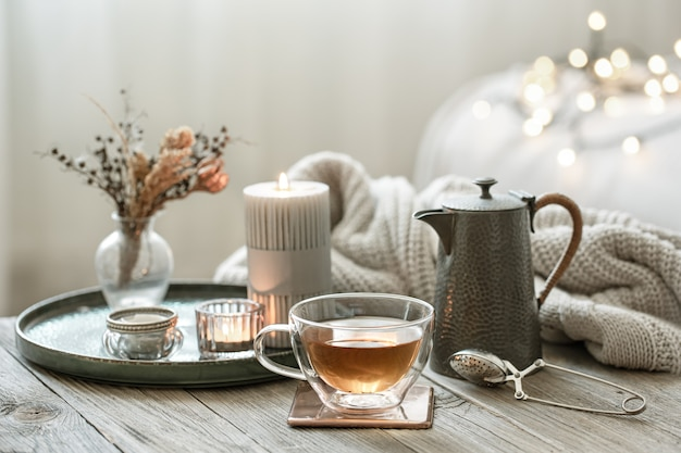 Cozy still life with a glass cup of tea, a teapot and candles