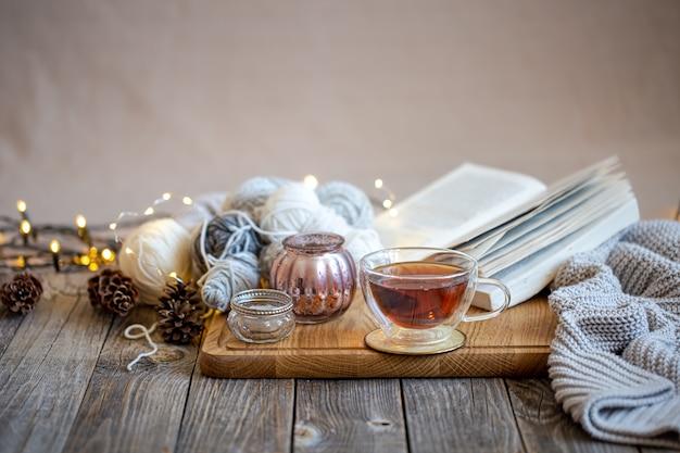 Уютный натюрморт с чаем и предметами декора, светящиеся огоньки в стене.